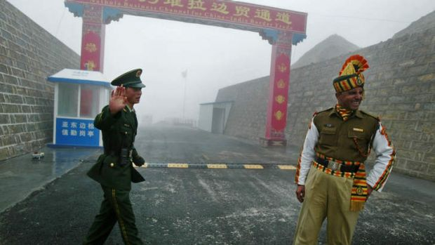 A Chinese soldier (L) and an Indian soldier stand guard at the Chinese side of the ancient Nathu La border crossing ...