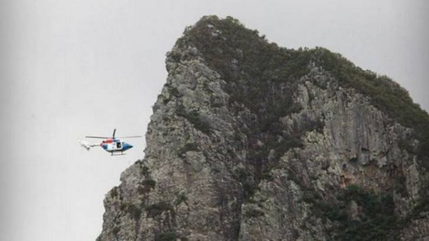 A helicopter moves in to rescue a female rock climber who fell from Mt Coonowrin in the Glasshouse Mountains.