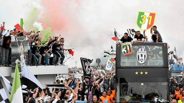 Party bus: Juventus players are mobbed as they bring the title back to Turin again, the first time in many years without ...