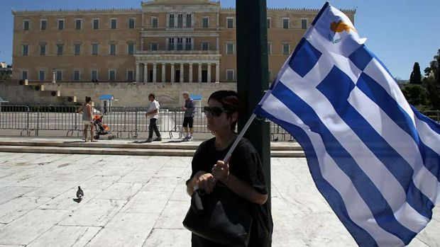 Protesting against austerity ... a woman holds Greek and small Cypriot flags during a rally in front of the Parliament ...