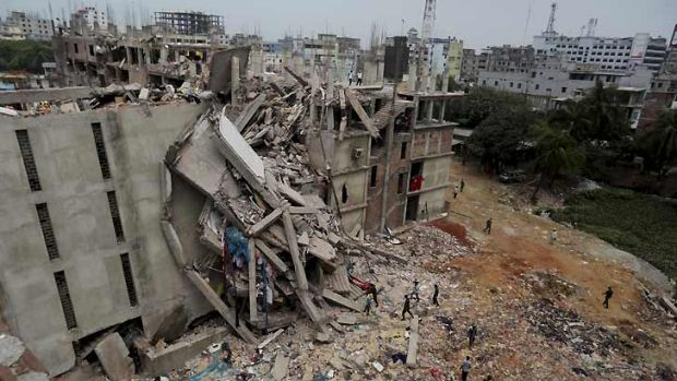 Hundreds dead ... Bangladeshi soldiers and rescue workers walk outside the collapsed building.