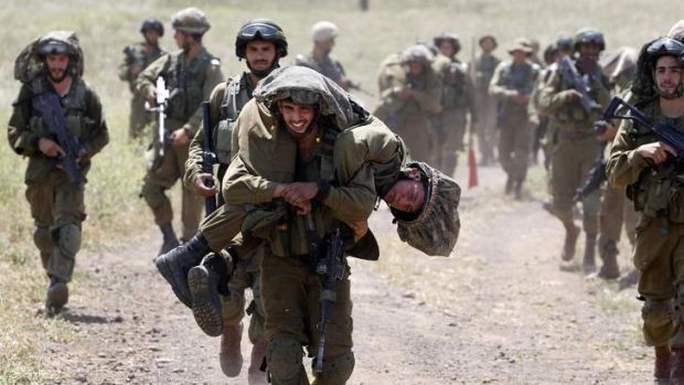 Right to strike: An Israeli soldier carries another soldier during training close to the ceasefire line between Israel ...