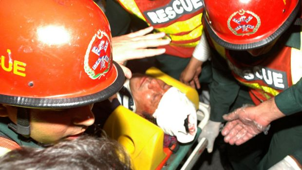 Rescue workers carry a bloodied Imran Khan to a Lahore hospital after he fell off a lift taking him onto the stage for ...