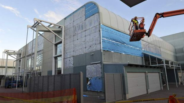 Asbestos cladding being removed from the exterior of the swimming pool building at the Australian Institute of Sport.