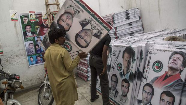 Party volunteers prepare  campaign posters of Imran Khan in Lahore ahead of Saturday's election.
