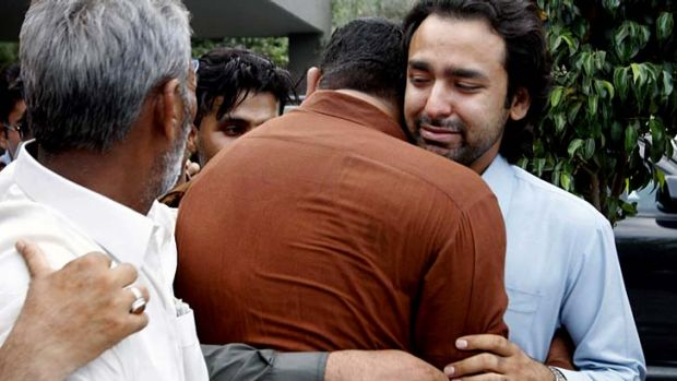 Signs of support: Musa Gilani, right, the brother of Ali Haider Gilani is comforted.