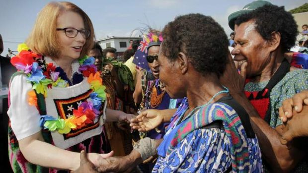 Happy days: Prime Minister Julia Gillard gets a colourful welcome as she mixes with local people at a market in Port Moresby.