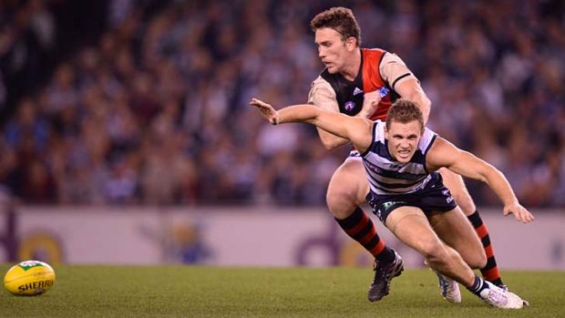 Geelong's Joel Selwood is pushed off the ball by Essendon's Heath Hocking.