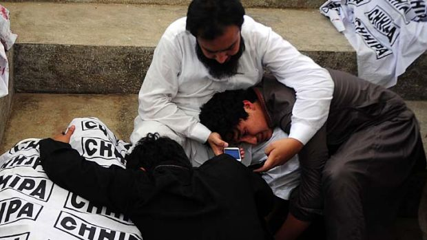 Election violence: Pakistani relatives mourn over the dead body of a blast victim at a hospital following a bomb ...