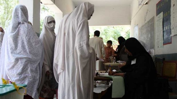Rizwana, second from the front, looking at camera, lines up to vote in Pakistan's general election on Saturday. More ...