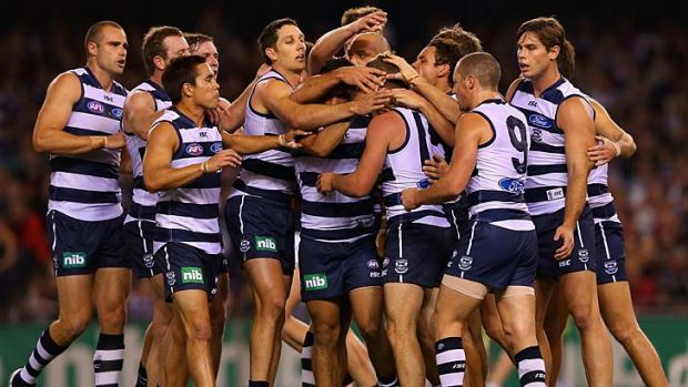 Jordan Schroder of the Cats is congratulated by his teammates after kicking a goal against Essendon.