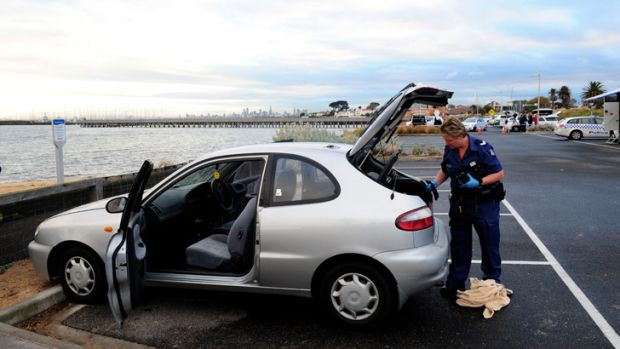 A police forensics officer examines a car parked near the foreshore.