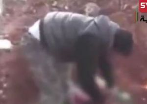 Still image of video of Khaled al-Hamad cutting heart and organs out of dead Syrian soldier.