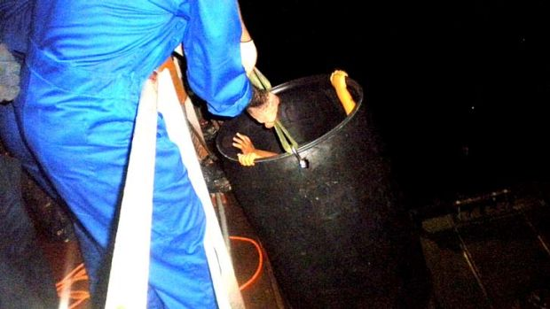 Children being rescued from the boat using a bucket.