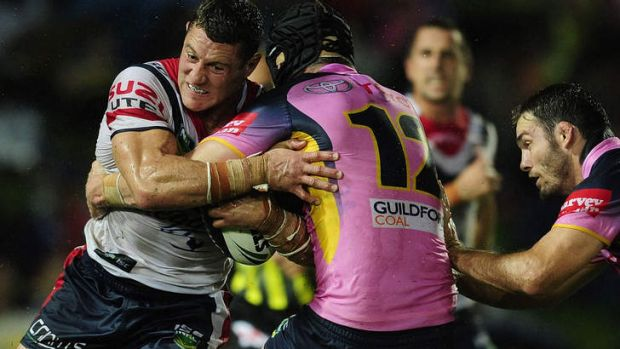 War of attrition: Luke O'Donnell of the Roosters is tackled by Gavin Cooper of the Cowboys.