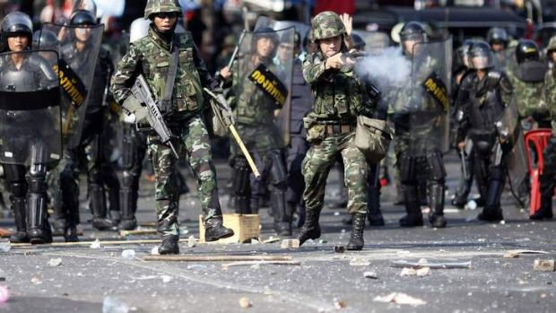 """Thai soldiers fire their weapons at anti-government """"red shirt"""" protesters during clashes in central Bangkok April 10, 2010."""