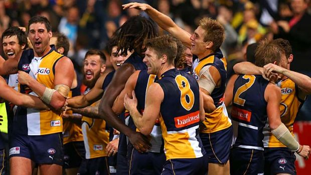Nic Naitanui is mobbed by his teammates after he kicked the winning goal against North Melbourne.