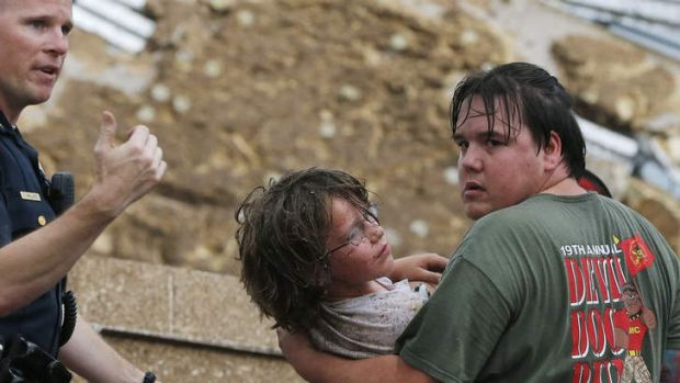 A child is carried from the rubble of the Plaza Towers Elementary School following the tornado in Moore, Oklahoma.