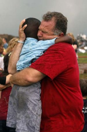 Horror: A teacher hugs a child at Briarwood Elementary school after the monstrous tornado flattened the building.