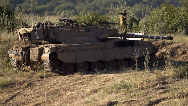 An Israeli soldier works on top of a tank in a position in the Israeli controlled Golan Heights, on the border with ...