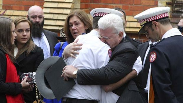 Emotional farewell: Robert Rossington is given his son Paul's hat at a memorial service.