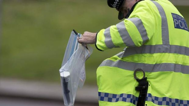 Grisly find: A police officer carries an evidence bag containing a knife near the scene of the killing.