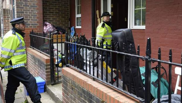 Police officers stand outside a block of flats in Greenwich following a raid in connection with the killing of a British ...