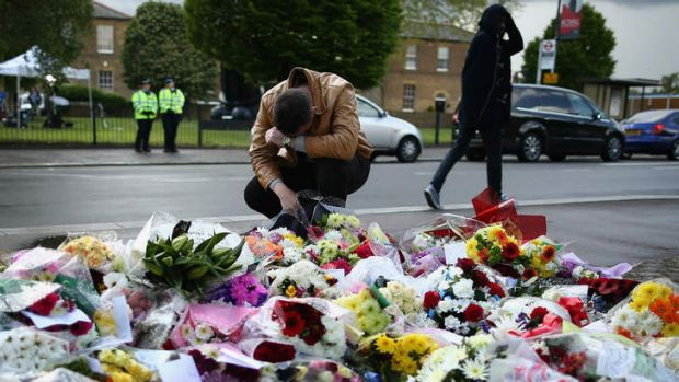 Floral tribute: a man at the scene of the killing.