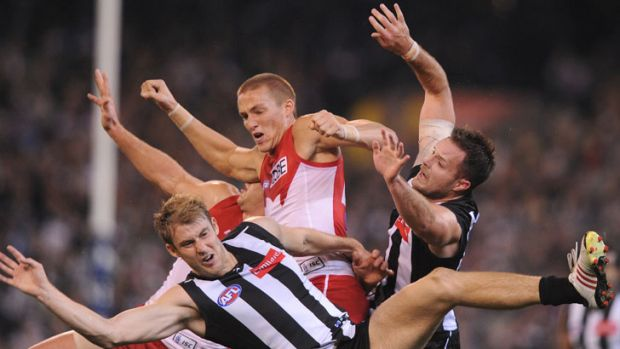 Sydney's Sam Reid crashes between Collingwood's Ben Reid and Nathan Brown