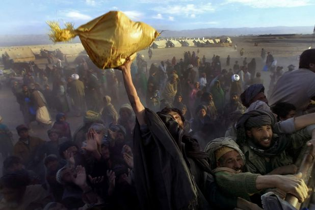 Afghan refugees at Kili Faizo refugee camp desperately reach for bags of rice and sugar being handed out by a local ...
