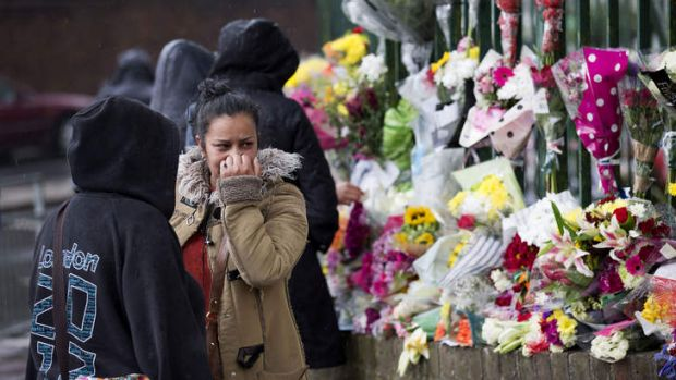 In tribute: A woman reacts after looking at flowers left for murdered British soldier Lee Rigby outside Woolwich Barracks.