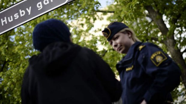 Stockholm riots: A policewoman speaks to a resident of Husby.
