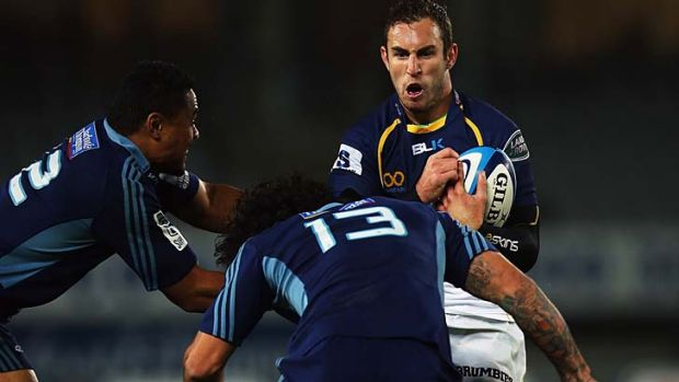 Tough rooster: The Brumbies' Nic White prepares to soak up another hit from the Blues' Rene Ranger on Saturday night.