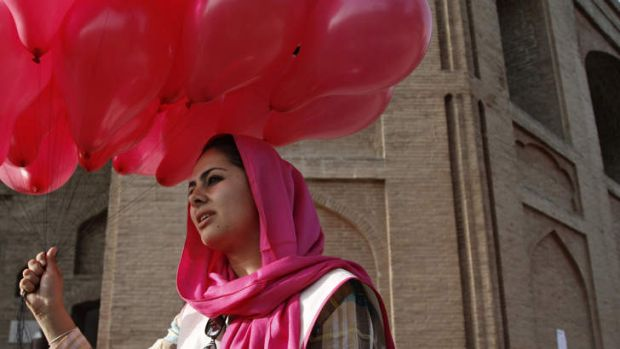 An Afghan woman holds a portion of some 10,000 pink balloons handed out by artists and activists in Kabul, Afghanistan, ...