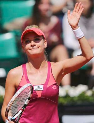 Agnieszka Radwanska waves to the crowd after defeating Shahar Peer of Israel in the first round.