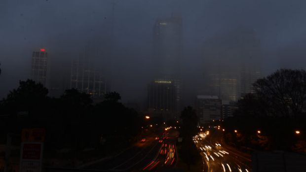 Fog covers traffic along the Cahill Expressway for a second morning in Sydney.
