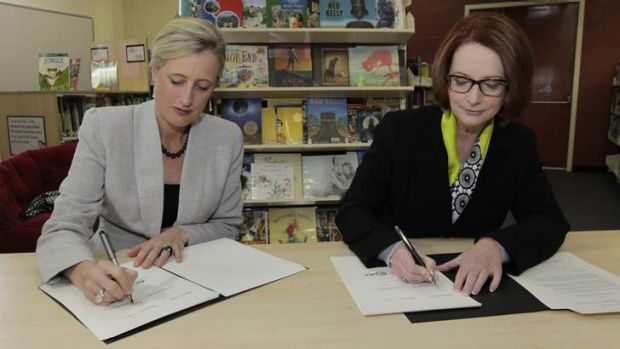 Prime Minister Julia Gillard signs the Gonski school funding agreement with ACT Chief Minister Katy Gallagher at Lyneham ...