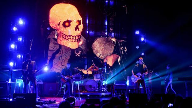 Queens of the Stone Age on-stage in LA with illustrator Boneface's menacing animations in the background.