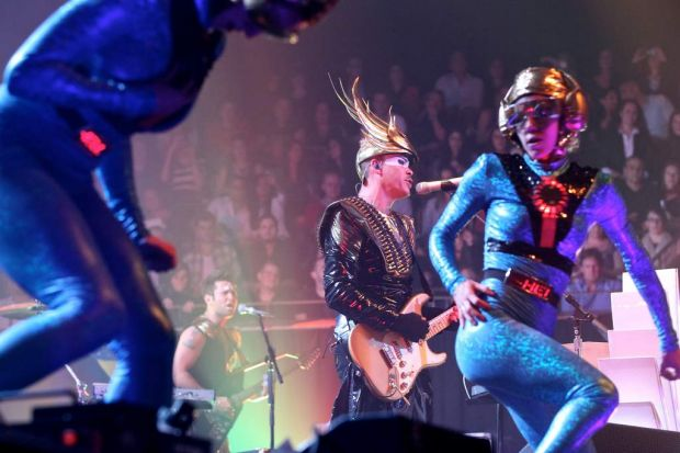 """Singer Luke Steele and guitarist Surahn """"Sid"""" Sidhu on stage with performers."""