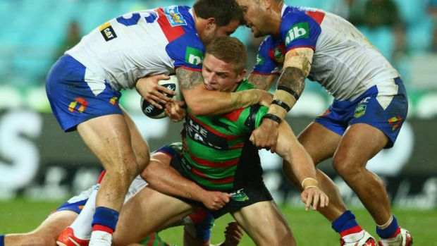 Crunched: Souths forward George Burgess is wrapped up by the Newcastle defence at ANZ Stadium.