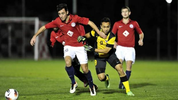 Canberra FC player James Field gets past Malaysia player Norshahrul ldlan Talaha on Thursday.