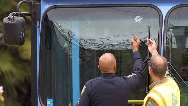 A police officer and a transit official look at a bullet hole, one of many, in a public transit bus in which two ...
