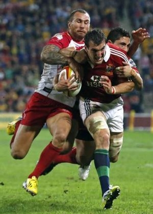 Double-teamed: Quade Cooper and Anthony Fainga'a tackle British and Irish Lions captain Sam Warburton.