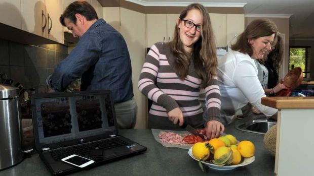 A TIME AND A PLACE: Georgie Sanderson, centre, helps out in the kitchen with her parents Grant and Jenny and friend ...