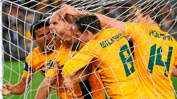 Net bulger: Mark Bresciano and the Socceroos celebrate scoring the opening goal against Jordan in Melbourne on Tuesday night.