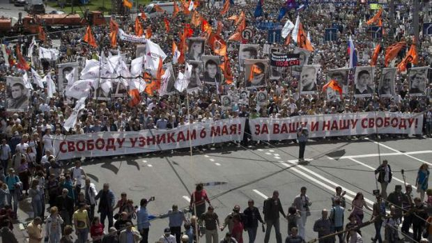 Russian opposition protesters some holding portraits of political prisoners  shout anti-Putin slogans as they march ...