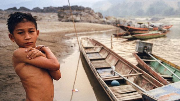 A boy stands on the banks of the Mekong River near the relocation site for a Lao village, which was moved to make way ...