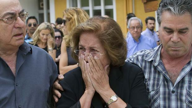 The mother, centre, and father, left, of Cypriot media boss Andis Hadjicostis leave the court after hearing the verdict.