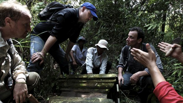 Rock gods: Australian archaeologist Damian Evans (blue cap) inspects a find with Jean-Baptiste Chevance (kneeling on the ...