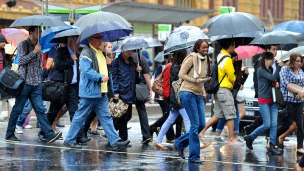 Commuters outside Flinders Street station as the rain pelted down earlier this year.